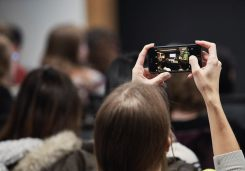 Image of a woman holding up a phone to take a photo of information on a screen during an industry workshop event