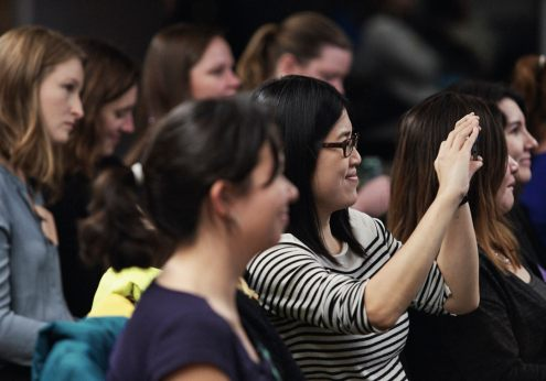 Image of a young woman in a striped shirt and glasses smiling while taking a photo during an industry workshop event