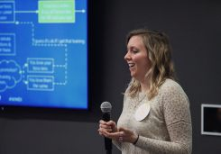 Image of a young woman giving a talk with a flow diagram on the screen behind her