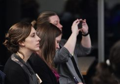 Image of women listening to a talk and taking notes and photos at during a workshop