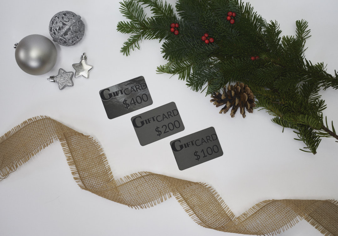 Gift cards surrounded by evergreen branches with red berries, burlap ribbon and silver Christmas decorations