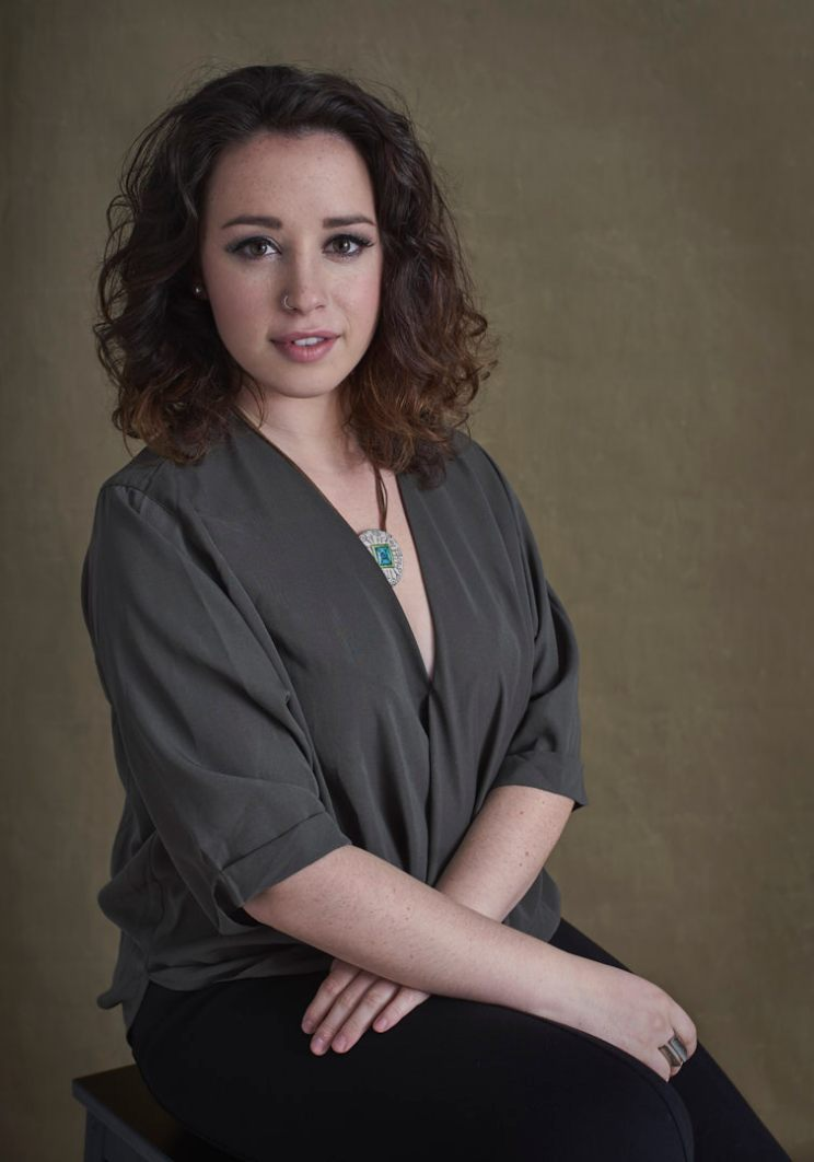 Studio portrait of a young woman with curly brown hair wearing a statement necklace resting her hands in her lap and smiling at the camera