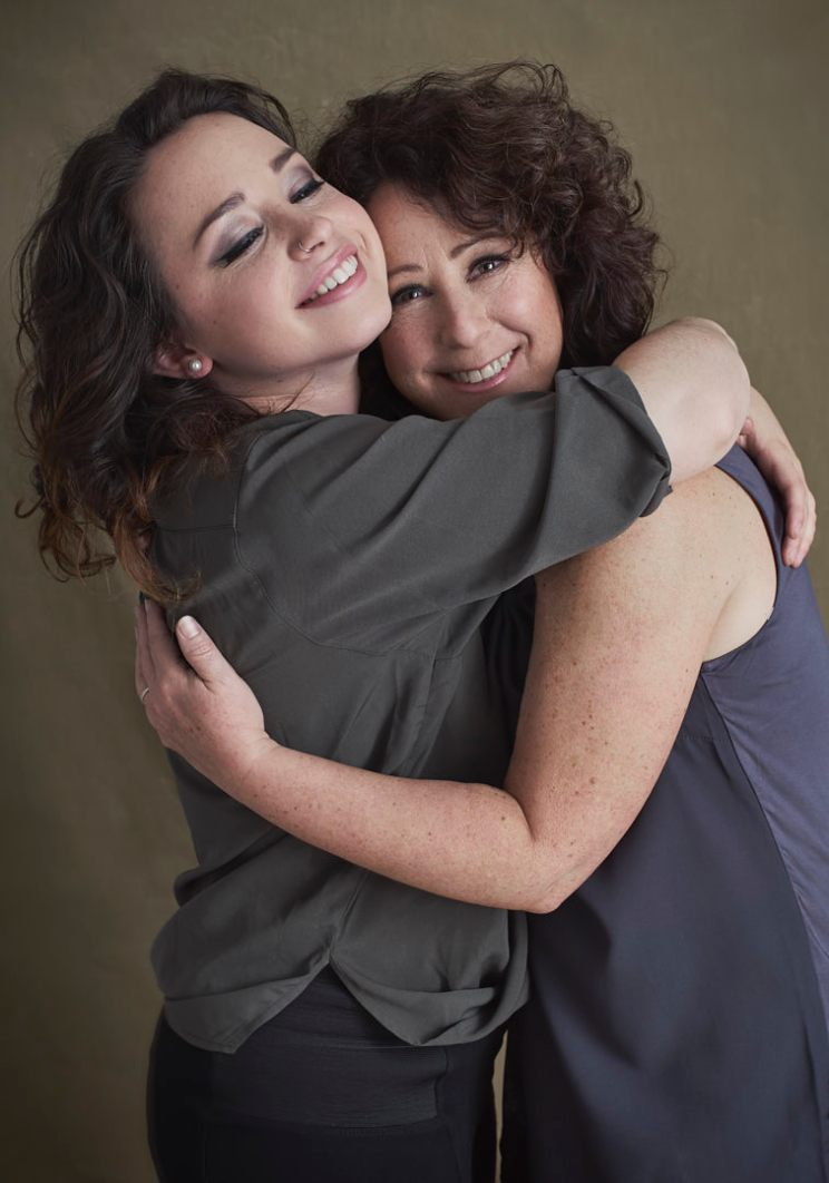 Studio portrait of a young woman smiling broadly with closed eyes bear hugging her mother who is smiling at the camera
