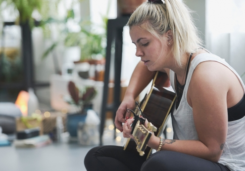 Image of a young woman sitting on a yoga mat playing a guitar and singing surrounded by plants in a yoga studio