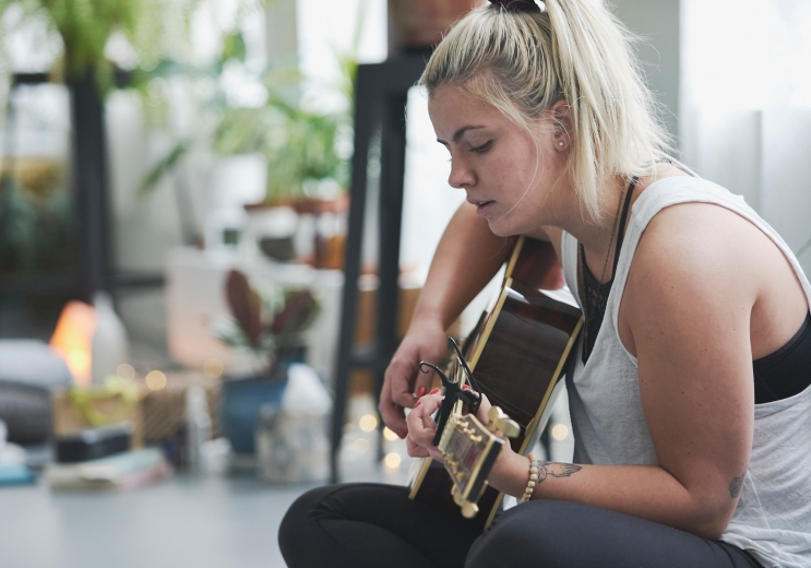 A young woman sitting on a yoga mat playing a guitar and singing surrounded by plants in a yoga studio at a mothers and daughters workshop in Vancouver focusing on relationships and self care by Vancouver workshop and retreat photographer Angela McConnell
