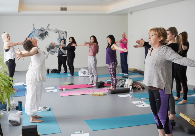 Image of a woman dressed in white leading a yoga exercise for a group of women at a mother and daughter retreat in Vancouver