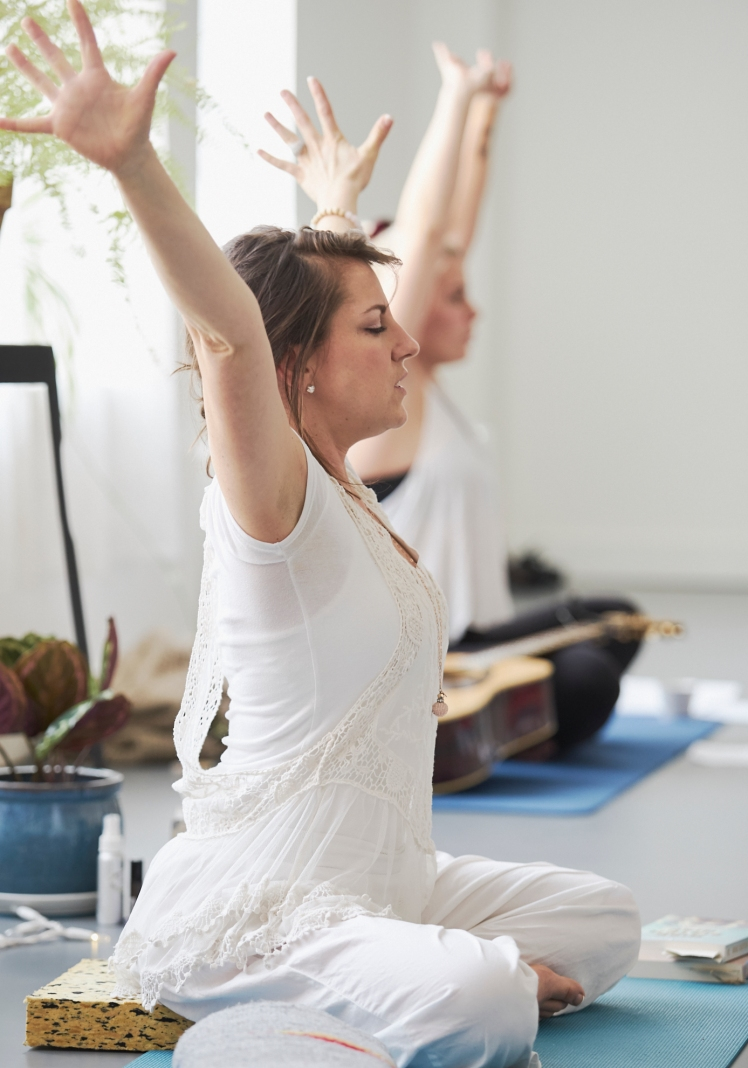 Image of a woman dressed in white sitting on a yoga mat directing a group of women at a mother and daughter retreat in Vancouver