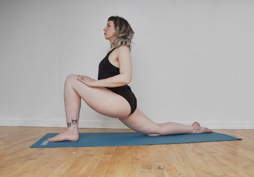 Self portrait of a woman with silver hair and tattoos doing a low lunge pose on a blue yoga mat
