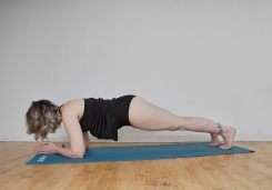 Self portrait of a woman with silver hair and tattoos doing low plank pose on a blue yoga mat