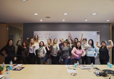 Image of a group of women in power poses in front of a whiteboard with empowering phrases during a self care workshop in Vancouver