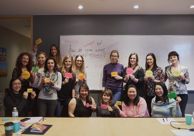 Image of a group of women holding up cards with empowering words during a self care workshop in Vancouver