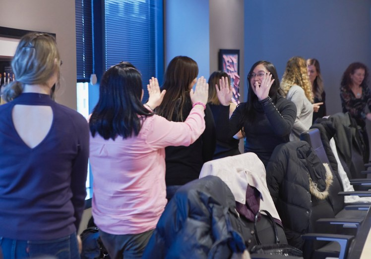 Image of women give each other a high five and laughing during a self care workshop in Vancouver