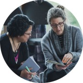 Image of two women comparing notes in journals during a group exercise at a workshop
