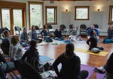 A yoga instructor sits in the middle of a room demonstrating a heart opening pose while leading a yoga session at a self care for educators workshop at Roundhouse Farm, Victoria BC
