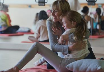 A woman sits on the floor smiling hugging her smiling daughter on her lap during a mother and daughter workshop in Vancouver focusing on relationships and self care