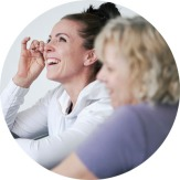 Image of a woman wiping tears away as she laughs while sharing in a group of women at a mother and daughter retreat in Vancouver